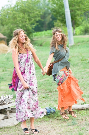 70s adult: Two Beautiful Hippie Woman Dancing in the Countryside,Italy Stock Photo