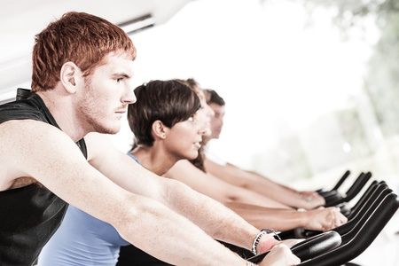 Group of five people in the gym, exercising their legs doing cardio training,Italy Stock Photo