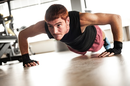 pushup: Strong, handsome man doing push-ups in a gym as bodybuilding exercise, training his muscles