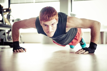 Strong, handsome man doing push-ups in a gym as bodybuilding exercise, training his muscles photo