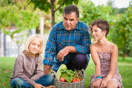 Adult Farmer with Children and Harvested Vegetables,Italy photo