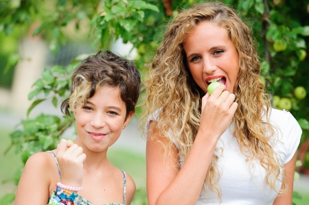 couples outdoors: Beautiful and happy young mother eating apple together with her small daughter  ,Italy Stock Photo