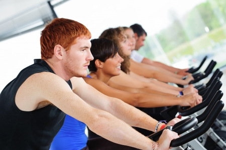 Group of five people in the gym, exercising their legs doing cardio training,Italy photo