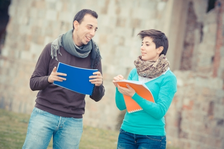 Two college students at park with books on hands, Italy