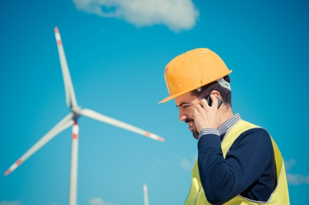 human energy: Technician Engineer in Wind Turbine Power Generator talk at phone Station, Italy Stock Photo
