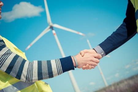 human energy: Engineers giving Handshake in a Wind Turbine Power Station Italy Stock Photo