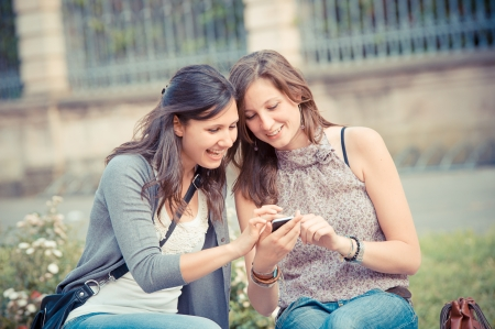 telephone together: Two shopping girls in park with a mobile phone, italy