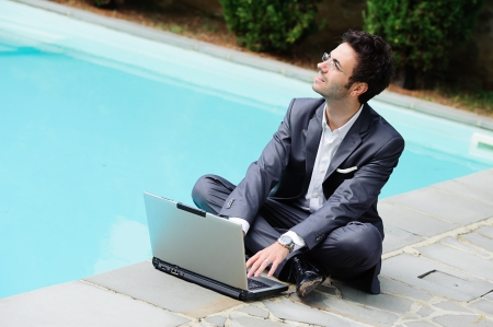 Young Businessman with Computer next to Swimming Pool Italy