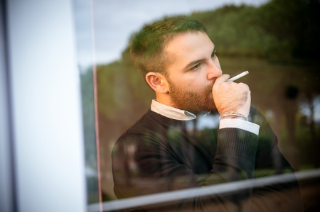 Worried man smoking a cigarette close to the window,Italy Stock Photo