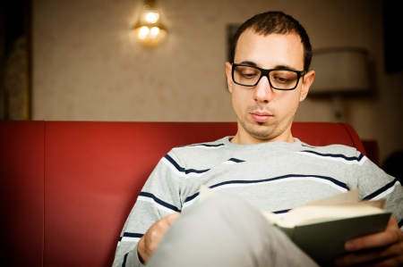 absorbed: Young adult man absorbed in the reading of a book,Italy Stock Photo