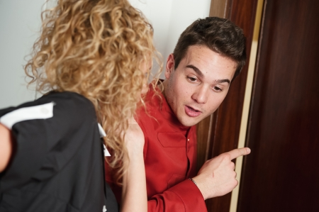 usher: Porter and hotel maid eavesdropping at the door,Italy Stock Photo