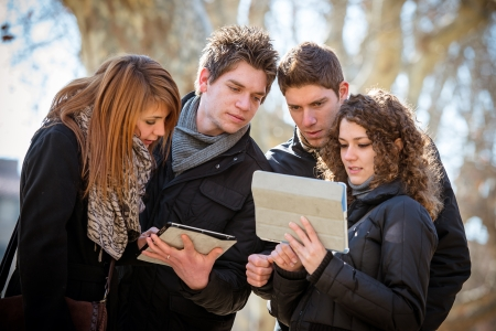 four friends: Friends looking at digital tablet,Italy