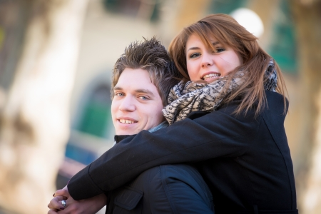 Happy couple piggyback hugging in wintertime park love smiling fun photo
