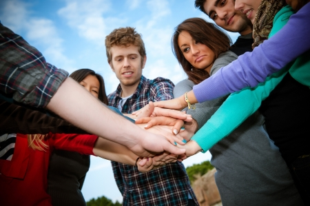 integrated group: Multiracial Students with Hands on Stack, Italy Stock Photo