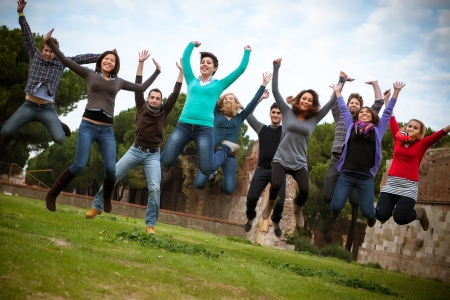 college campus: Group of Happy College Students Jumping at Park,Italy