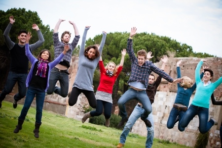 Group of Happy College Students Jumping at Park,Italy photo