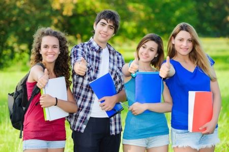 Young group of happy students showing thumbs up sign together outdoor in the park Standard-Bild