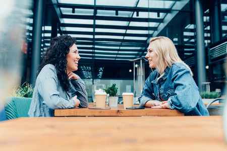 two friends talking: Two friends talking and drinking coffee, sitting in a cafe outdoors