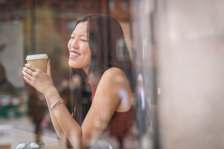 young chinese woman sitting next to windows in cafe. Standard-Bild