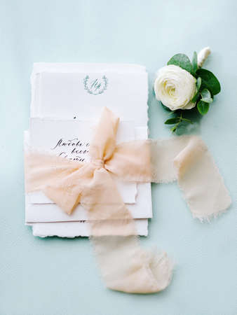 Wedding calligraphy on pale blue background with peach ribbon and a flower in white and green tones. Wedding decoration with invitation. Wedding blog concept. Handwriting calligraphy.