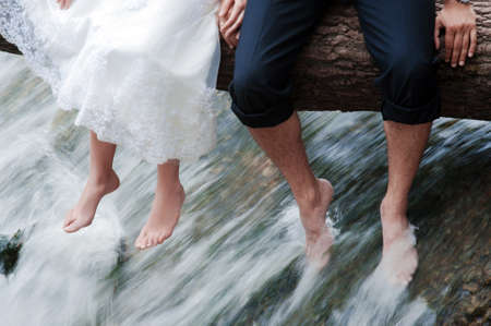 Summer wedding concept. Bride and groom sit bathing in the river. Happy couple.