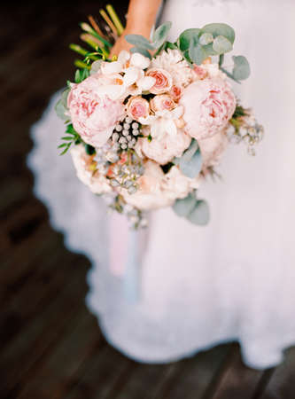 Beautiful wedding bouquet in the hands of the bride, modern stylish wedding concept, roses, peopy, eucaliptus, classic floristic style, spring wedding, copy space