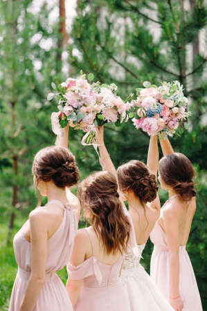 Bridesmaids in rosy dresses holding wedding bouquets outdoor on green background. Happy summer wedding concept.