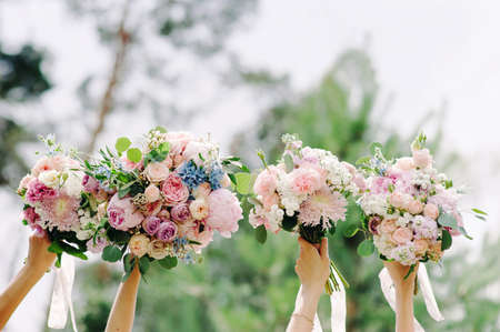 Bridesmaids holding modern wedding bouquets outdoor at the pine forest. Wedding bouquets with pink roses, white ranunculus, purple peonies flowers. Happy wedding concept. Copy space Foto de archivo