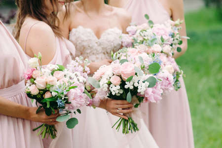 Bridesmaid's bouquets, wedding bouquets close up. Stylish wedding. Contemporary fashion wedding trends. Elegant beautiful style. Modern wedding concept. Bridesmaids holding wedding bouquets outdoor. Happy wedding concept.