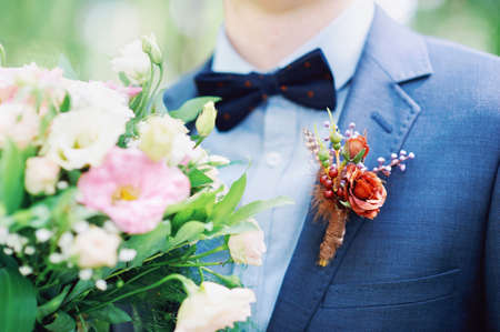 Wedding details close up. Groom in blue suit wearing boutonniere with red flowers and holding bridal bouquet