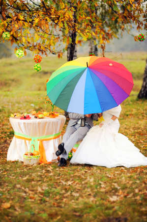 Autumn wedding. Outdoor portrait of newlyweds sitting under bright colorful umbrella (rainbow) in autumn park with yellow leaves.