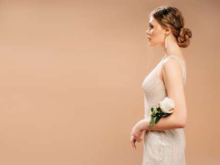 Bridesmaid's dress for ivory wedding. Beautiful bride in shining wedding dress with white rose in her hands. Attractive portrait in studio at neutral background with copy space.