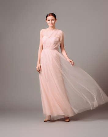Bridesmaid's dresses. Elegant moscato dress. Beautiful pink chiffon evening gown. Studio portrait of young happy ginger woman. Transformer dress idea for an event.