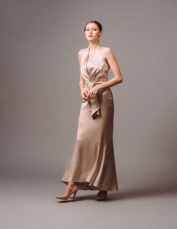 Bridesmaid's dresses. Elegant moscato dress. Beautiful ivory silk evening gown. Studio portrait of young happy ginger woman. Transformer dress idea for an event.
