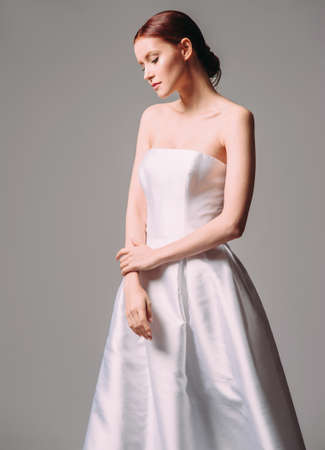 White glossy wedding dress. Studio portrait of beautiful young bride. Classic wedding style. Marriage day.