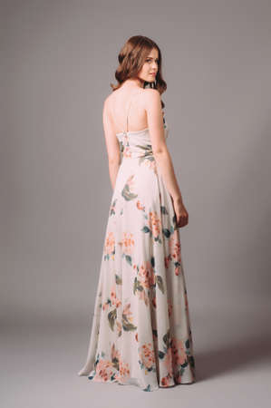 Brunette young woman in white sundress with floral print. Calm studio portrait of young lady in long backless evening gown on gray background. Standard-Bild