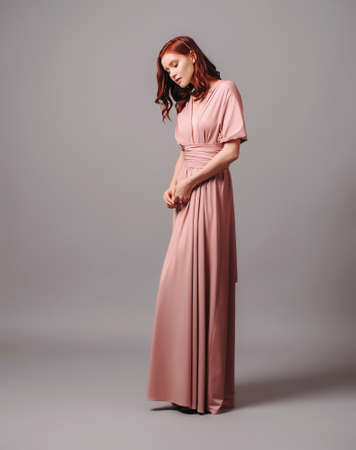 Bridesmaid's look in dust pink. Young ginger woman in summer transformer evening dress and high heel shoes on gray background at studio. Gorgeous lady.