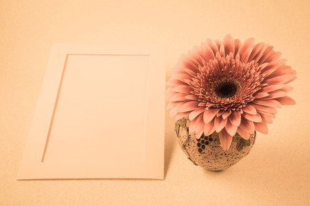card with gerbera flower in a small vase for congratulations with  light blank background Stock Photo
