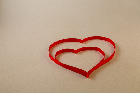 A single red heart of ribbon on a light beige background