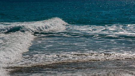 The surf of the blue turquoise sea with white perpendicular waves on the sandy beach. Kassandra, ? Chalkidiki, Greece