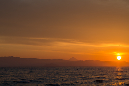 Spring orange dawn on the shore of the calm sea during the tide. Halkidiki. Greece