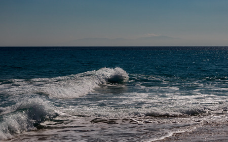 The surf of the blue turquoise sea with white perpendicular waves on the sandy beach against a bright clear sky. Kassandra, Chalkidiki, Greece