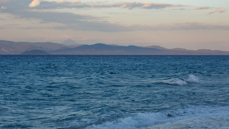 eventide: Evening storm on the blue sea overlooking the sky and mountains of the other shore, Kassandra, Greece Stock Photo