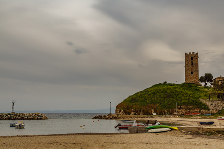 briny: Byzantine tower on a hill by the sea and against a cloudy sky and beach with boats, Nea Fokaia, Greece