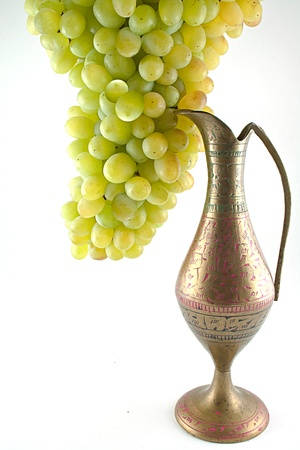 White grapes and stone jug isolated on a white background photo
