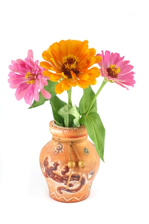 Zinnia flowers in a clay vase photo