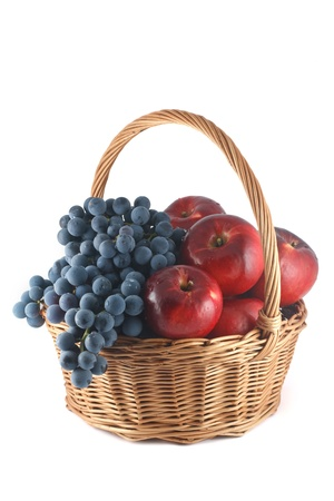 Wicker basket with red apples and blue grapes photo