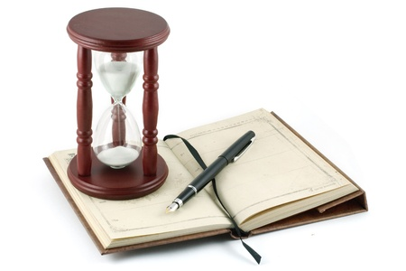 Hourglass, fountain pen and a notebook Stock Photo