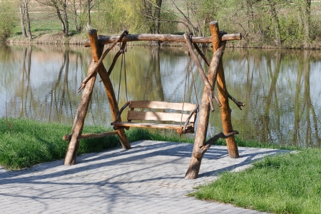 Wooden swing on the lake photo
