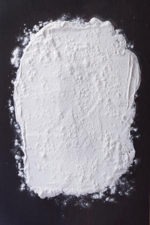 harina: harina blanca rociada sobre una mesa de madera oscura. vista desde arriba